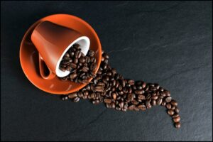 cup with spilled coffee beans