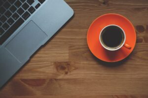 cup of coffee on table next to laptop